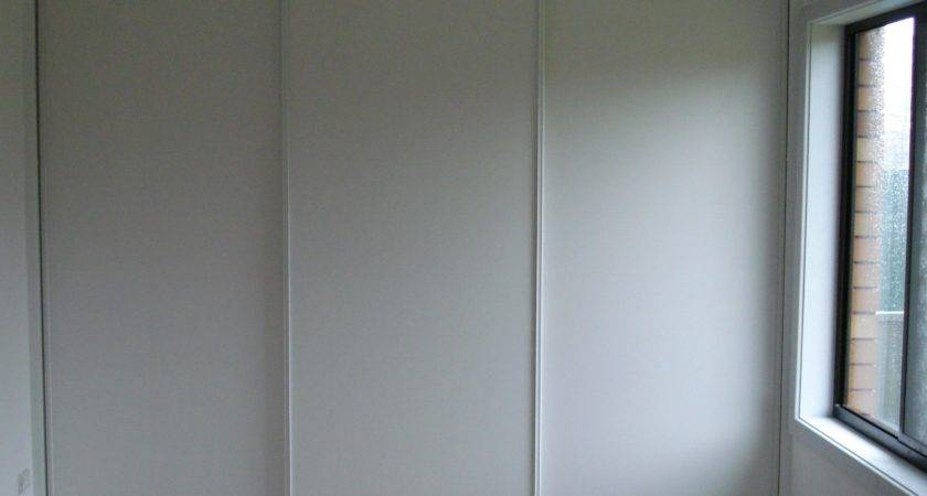 Three White Wooden Sliding Closet Doors Placed