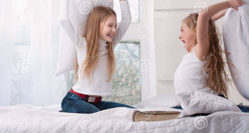 Two Girls Sitting Pillow Fight Bed
